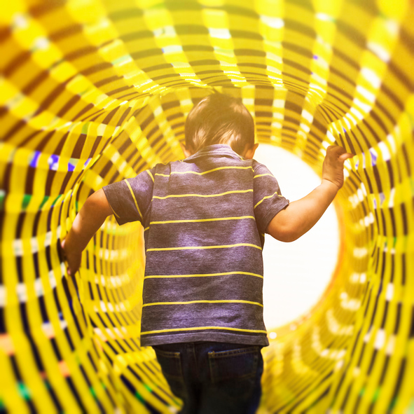 the concept of the transition bridge between the different dimensions of space. a child comes in bright colorful tunnel, view from the back